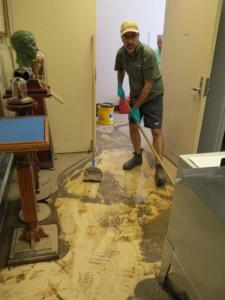 Ewen McPhee cleaning mud from the floors of the collection room.