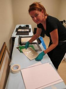 Dr Jo Wills removing water affected items from sleeves and drying on blotting paper.