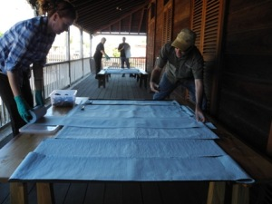 Jo Wills and Ewen McPhee cover fly screens with absorbent material to make a drying station. (Photo: Helen Pithe).