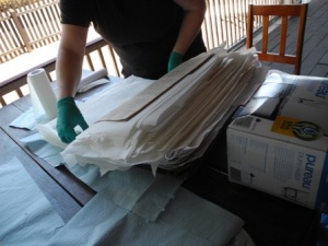 Interleaving a ledger with paper towels to help the drying process. (Photo: Helen Pithe).