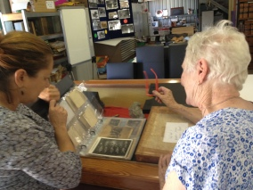 Sue shows Helen an archival album for cards and photographs.