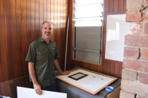 Ewen McPhee framing inages for the exhibition. Photo: Kate Eastick.