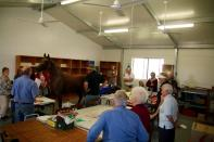 Visitors receiving on update on restoration and conservation of objects in the workshop