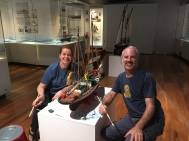 Jo and Ewen cleaning wooden lugger model