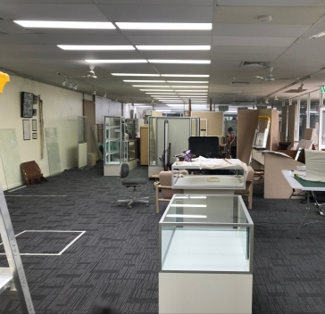 Showcases and large objects clustered at one end of the display space, leaving the other end free for planning and working
